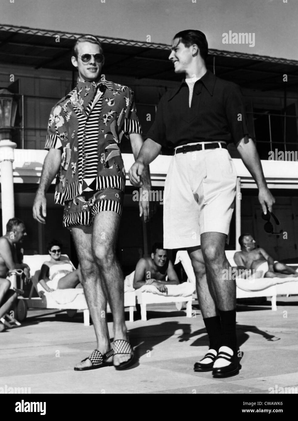 Men wearing the latest beach fashions. On the left, a colorful Mexican design; on the right, longer shorts and an - Stock Image