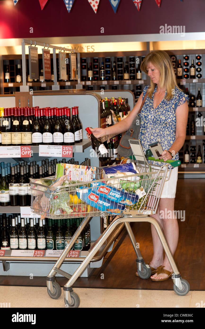 Supermarket wine department female shopper selecting a bottle of wine - Stock Image