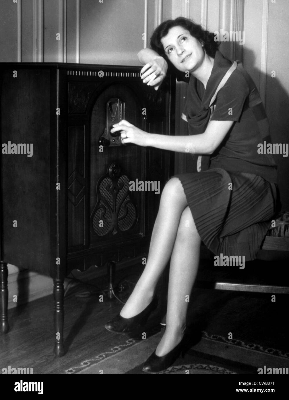 Woman listening to a radio, c. 1930s. - Stock Image
