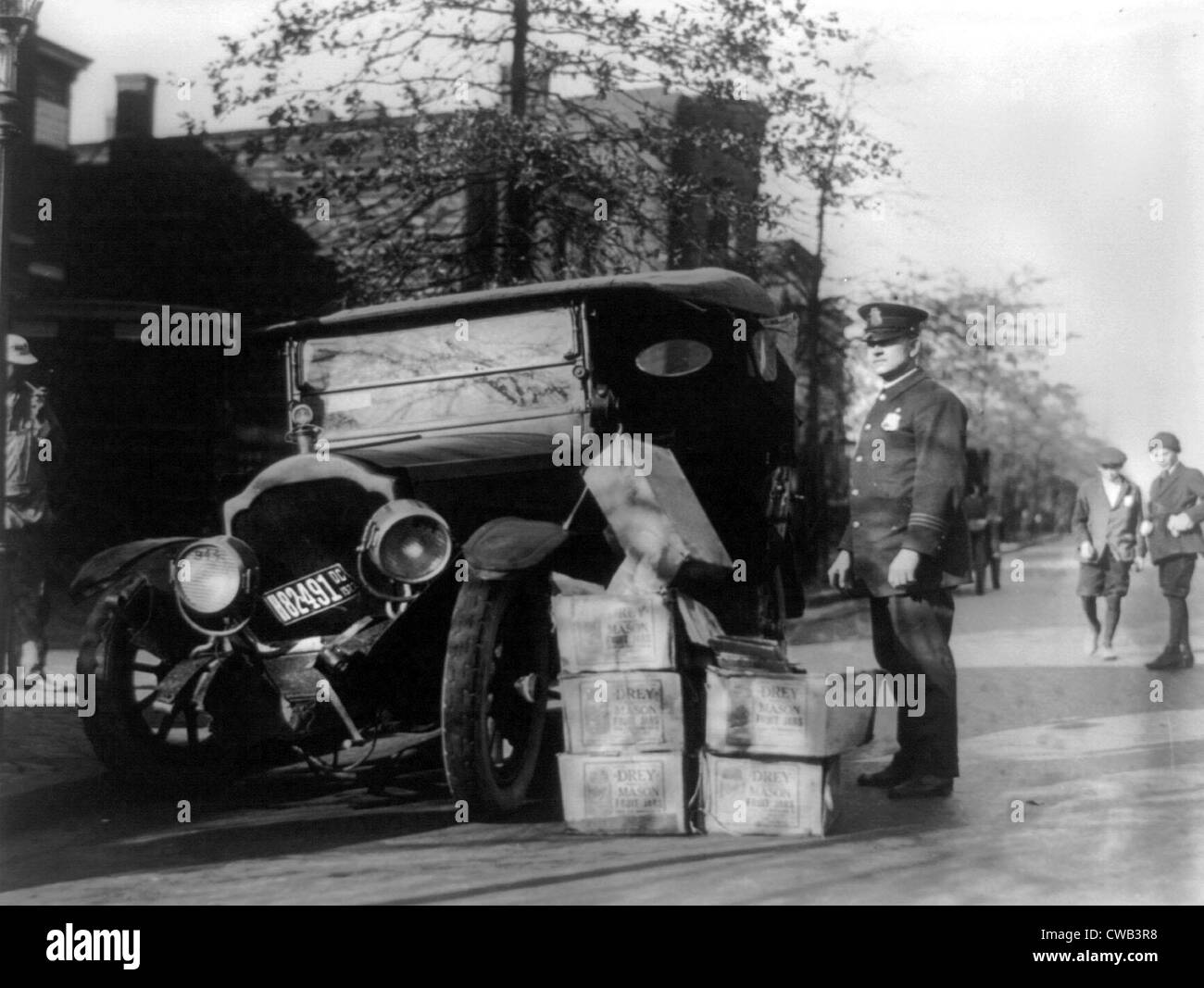 Prohibition, a policeman standing alongside a wrecked car and cases of moonshine, November 16, 1922. - Stock Image