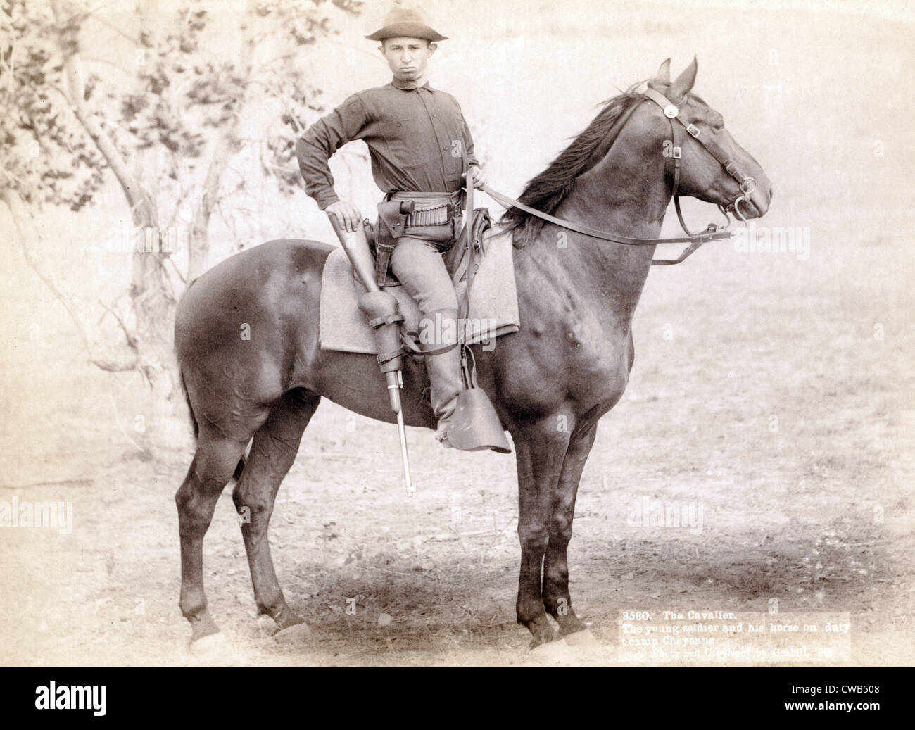 Wild West. The Cavalier. The young soldier and his horse on duty at camp, Cheyenne. photo by John C. Grabill, 1890 - Stock Image