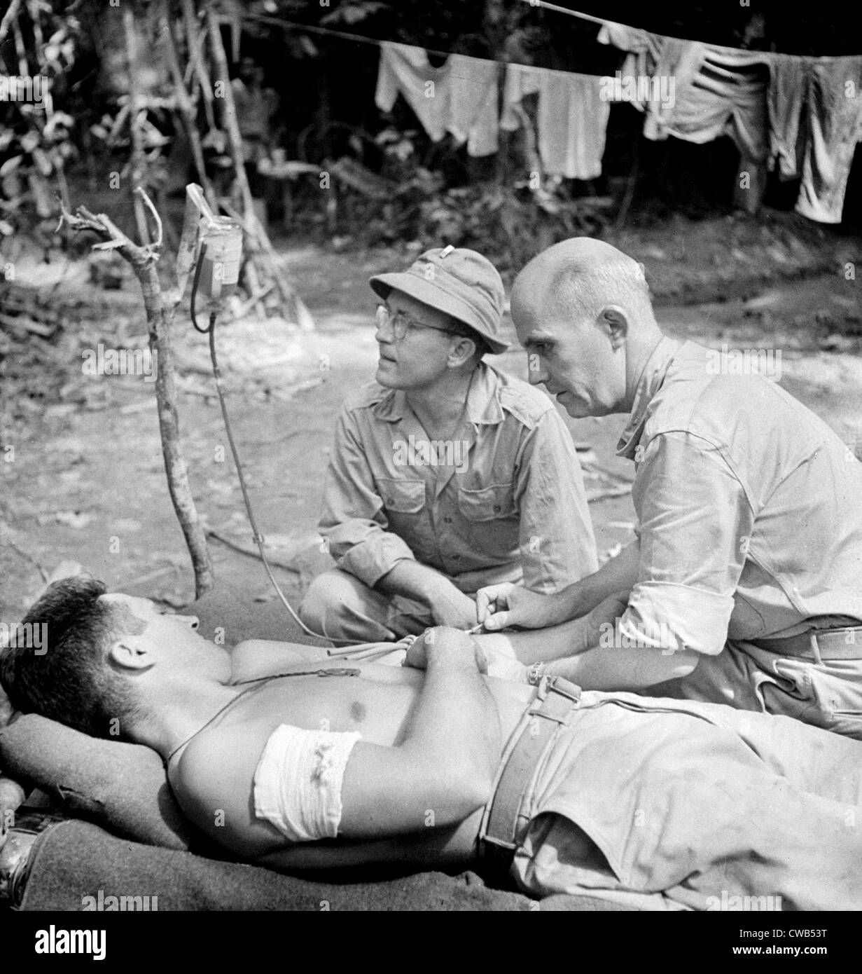 Blood Transfusion. A wounded man behind the lines on the Buna front being given a blood transfusion. Buna, New Guinea. - Stock Image