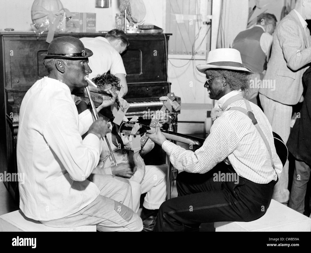 Folk Music. Itinerant laborers in blackface provide music for dancing at Shafter camp for migrants. Halloween party, - Stock Image