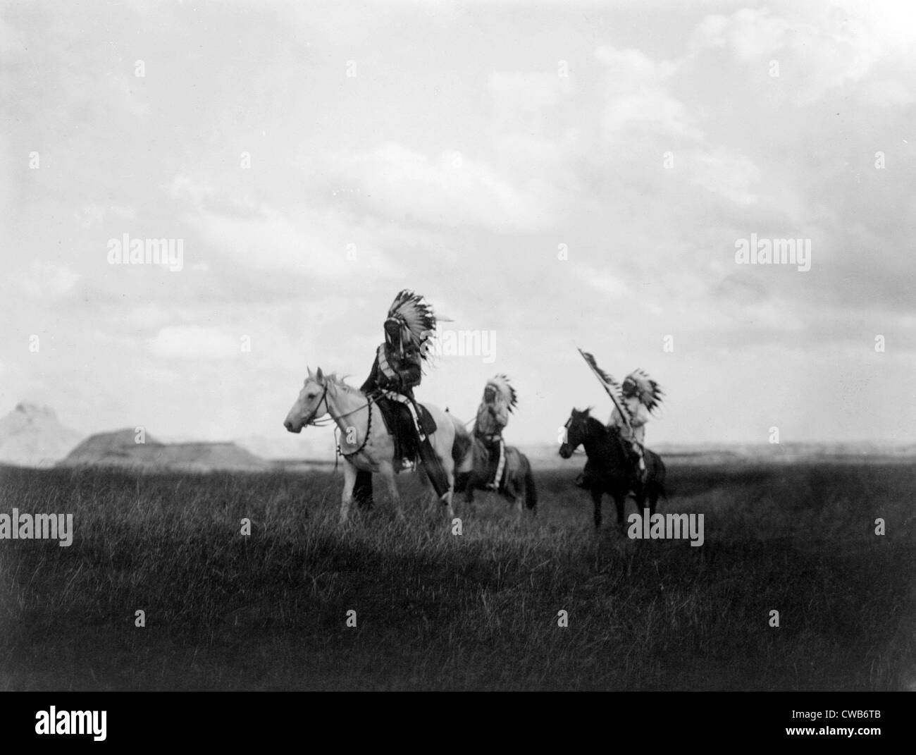 The March of the Sioux, three Sioux Indians on horseback on plains with rock formations in background, photograph - Stock Image