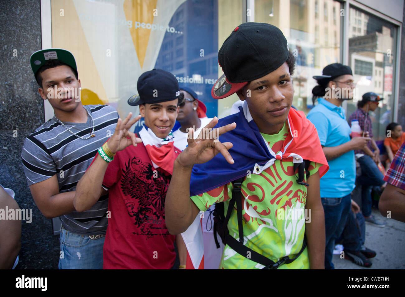 A group of energetic young teens on Avenue of the Americas for the Dominican Day Parade in New York City. - Stock Image