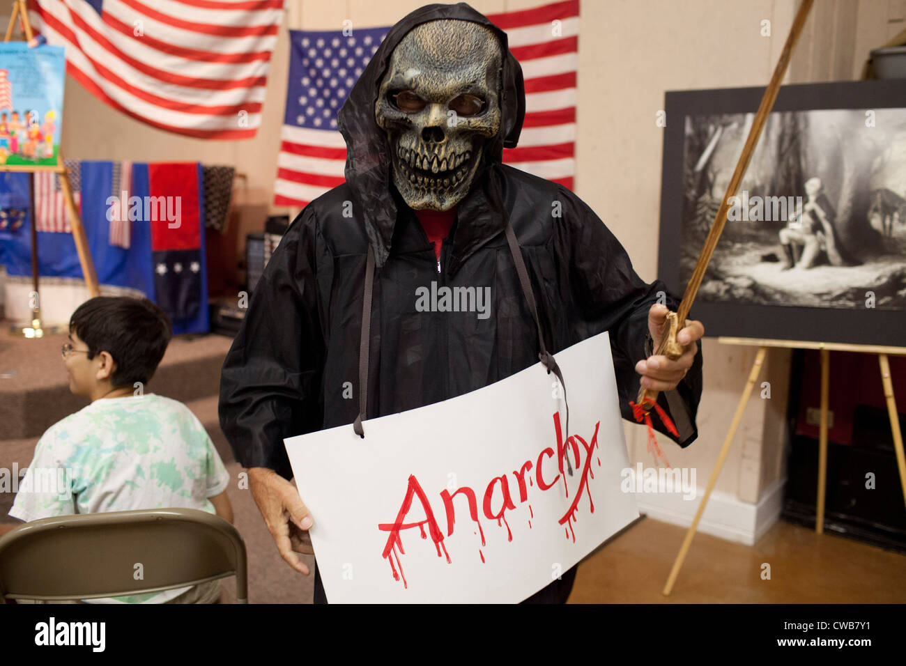 Volunteer dressed as ghoulish 'Anarchy' helps teach lesson on balancing tyranny and anarchy in order to - Stock Image