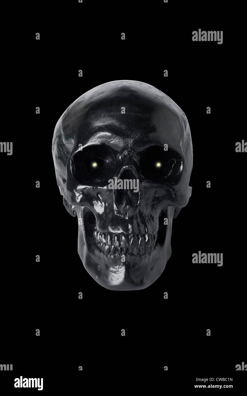 Black skull with glowing eyes isolated on black background - Stock Image