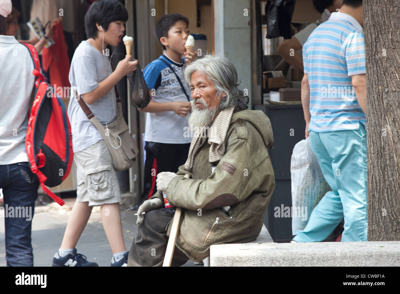 A homeless korean man wearing a heavy coat sits among all the people on a hot summer day. - Stock Image