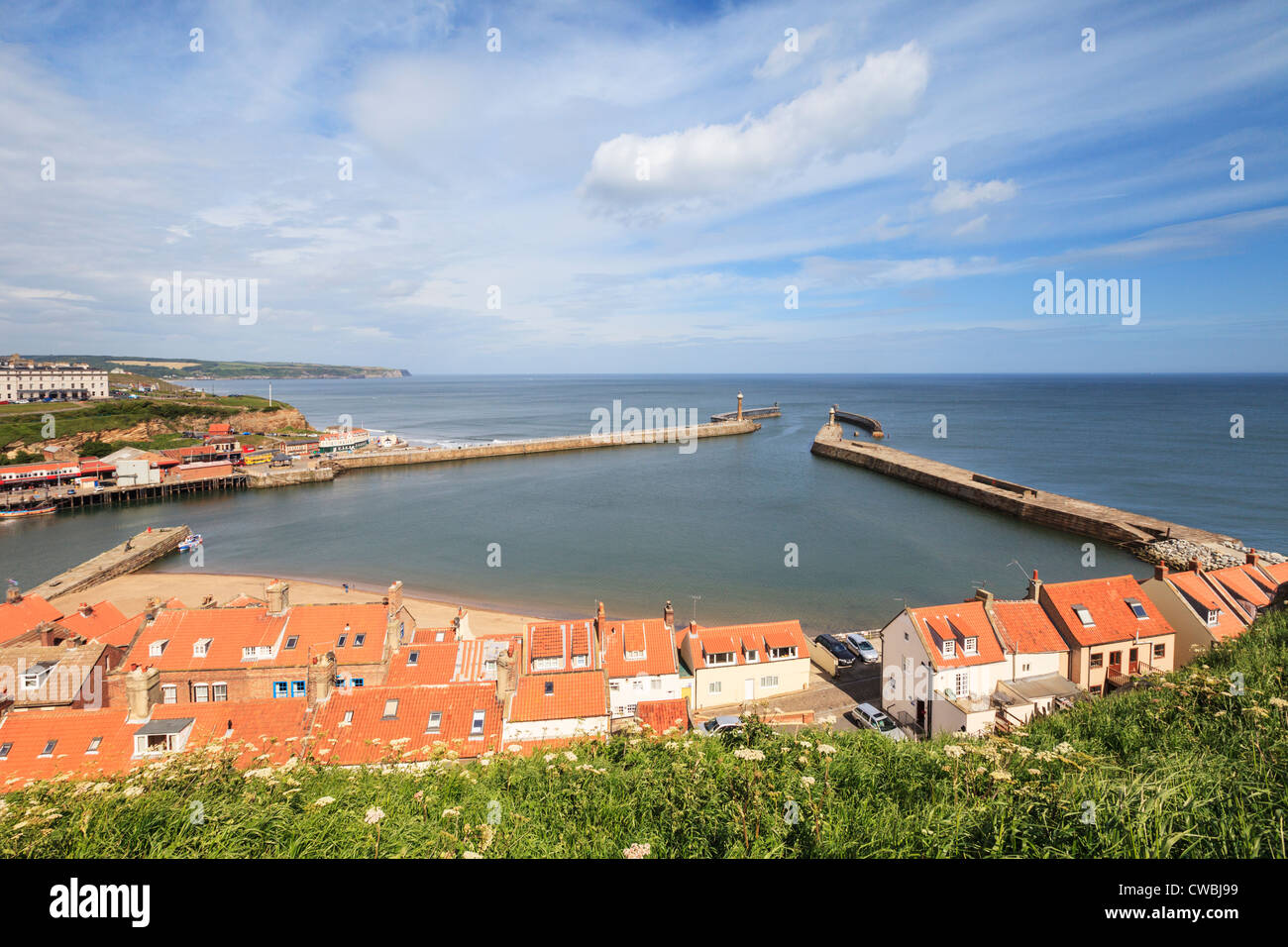 View across the harbour mouth at Whitby, North Yorkshire, on a Spring evening. - Stock Image