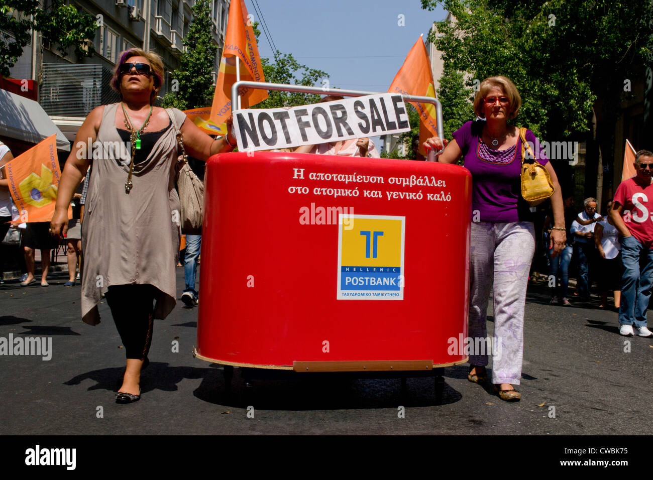Employees at the Hellenic Postbank march against the upcoming privatization of the bank. They carry a giant money - Stock Image