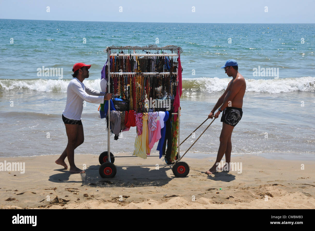 Two men moving beach cart ,displaying various colorful items for sale, along sandy beach, next to calm sea, Punta - Stock Image