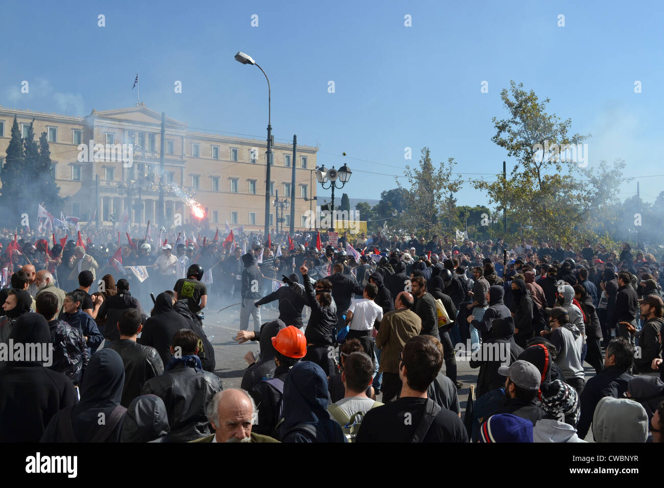 Anarchists clash with communists in front of the Greek Parliament during a general anti-austerity strike in Athens. - Stock Image