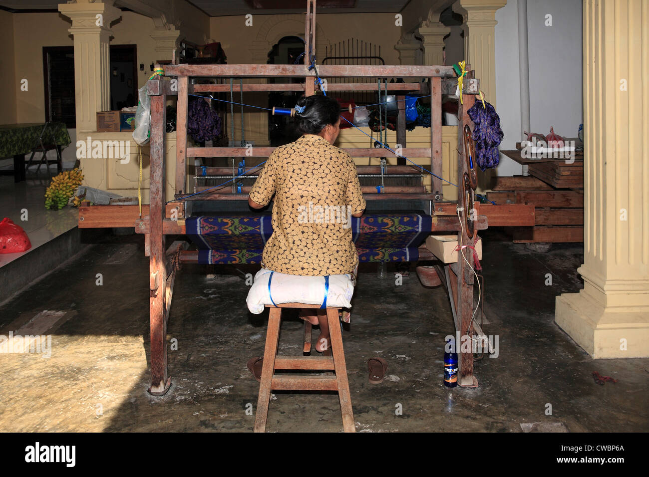 A process of Ikat fabric weaving. Weaving on a footloom. - Stock Image