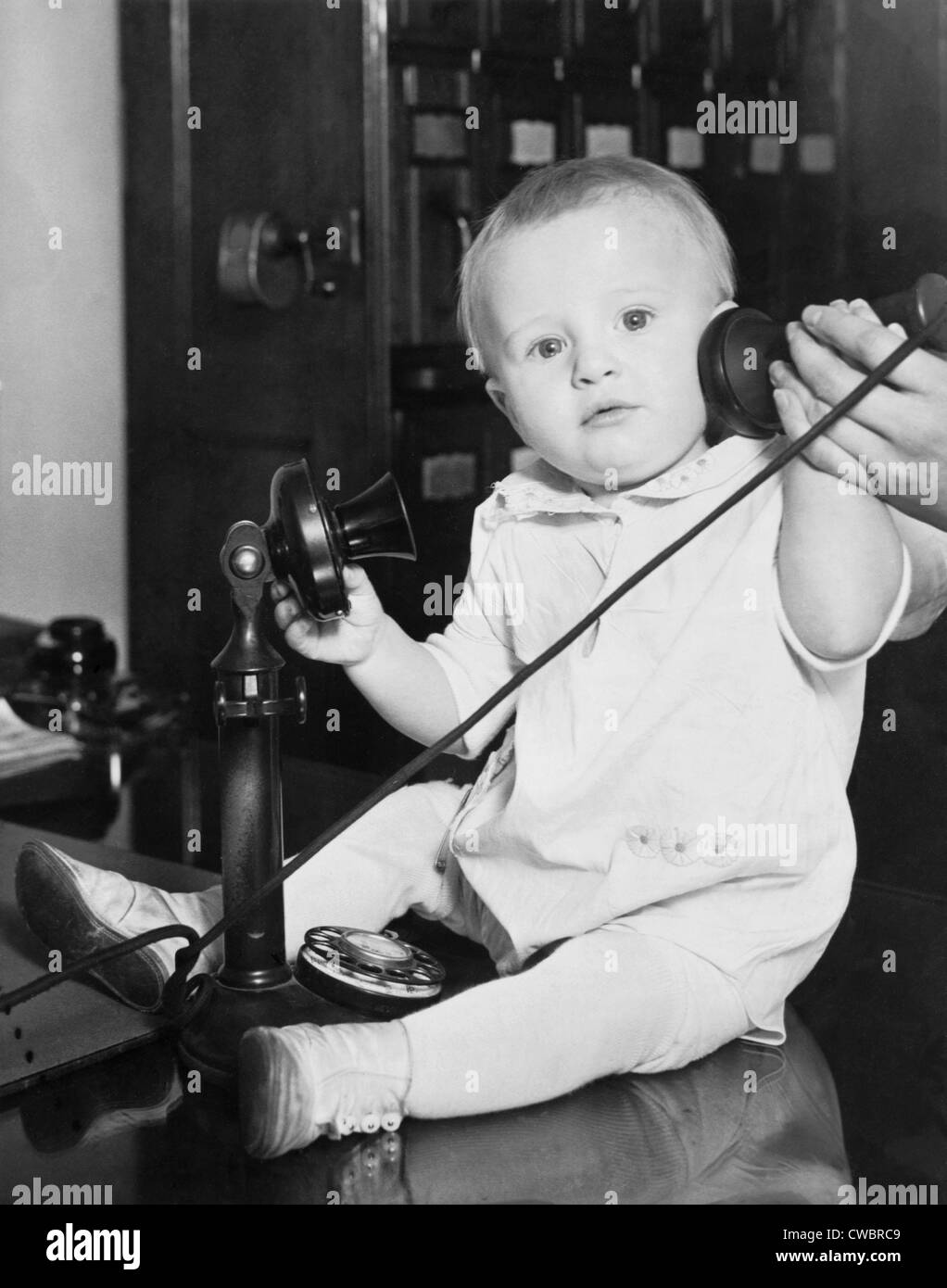 A baby found under a bed at the Stevens Hotel, Chicago, Illinois was photographed with a telephone to illustrate - Stock Image
