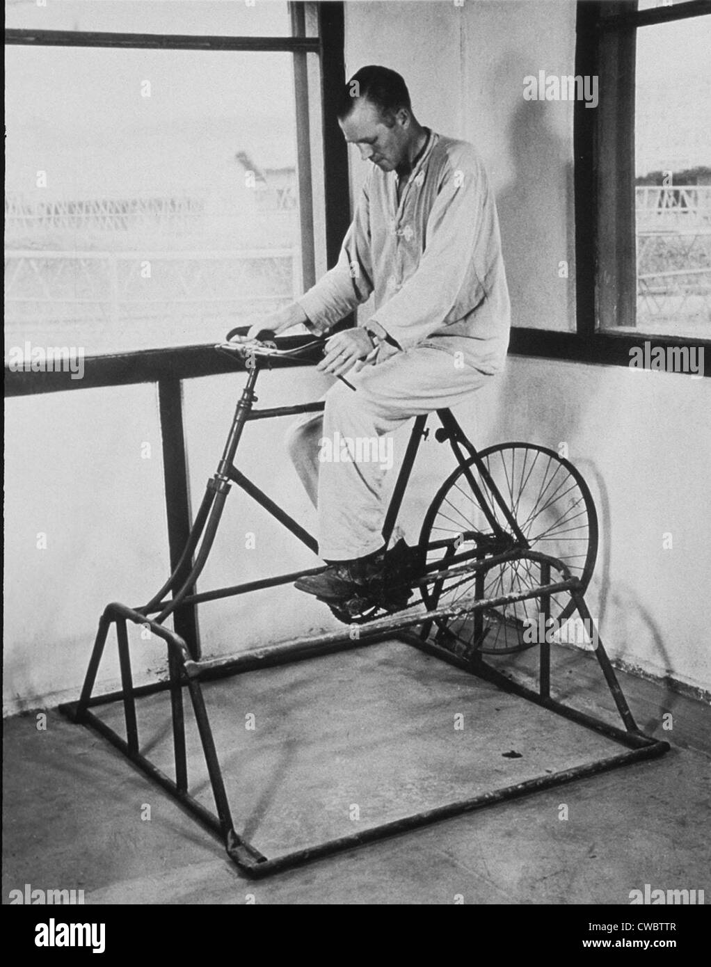 Physical therapy patient using stationary bicycle. Ca. 1950. - Stock Image