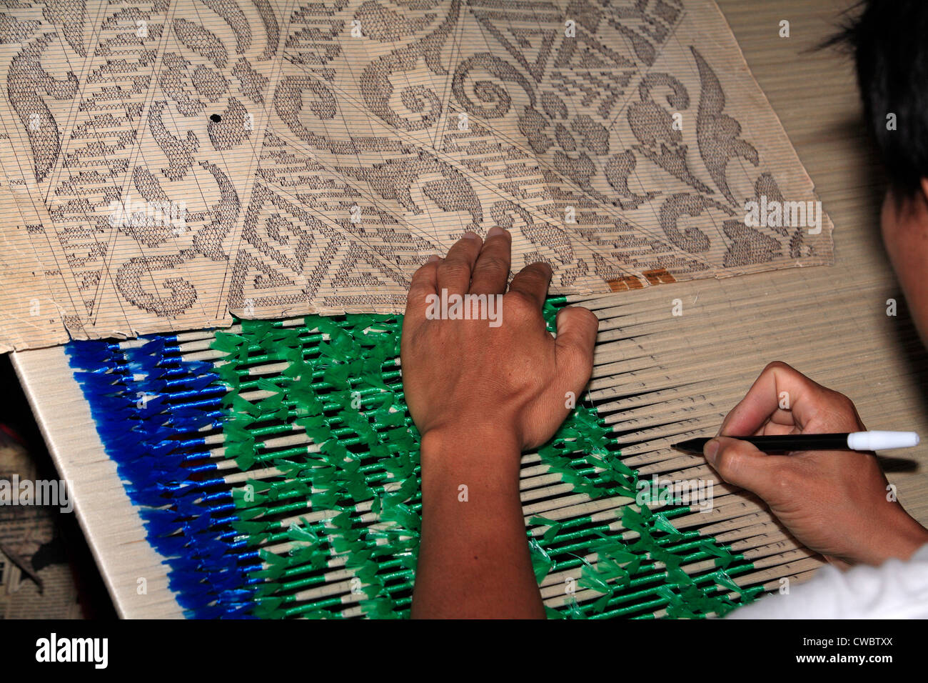 A process of Ikat fabric weaving. Preparing the thread for dyeing. - Stock Image