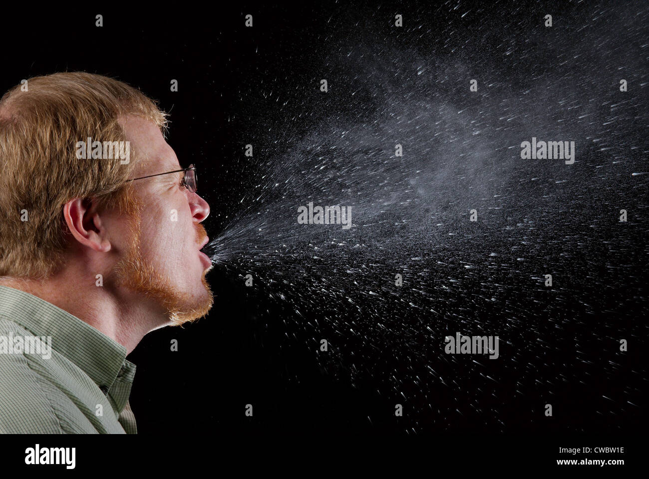 Sneeze in progress, revealing the plume of salivary droplets expelled from this man's open mouth. Photo by James - Stock Image