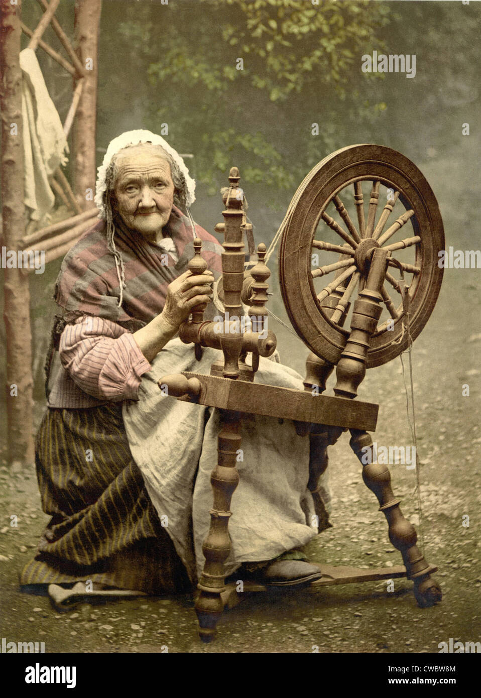 Elderly Irish Spinner working outdoors at her spinning wheel in the late 19th century.  While picturesque, home - Stock Image