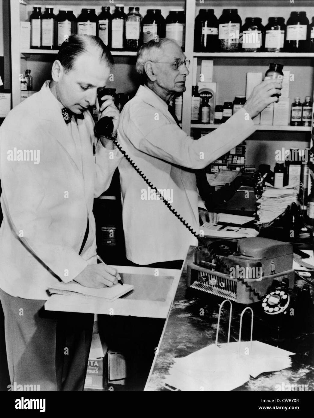 A pharmacist demonstrates the use of an early phone answering machine, a telephone disc prescription recorder, as - Stock Image