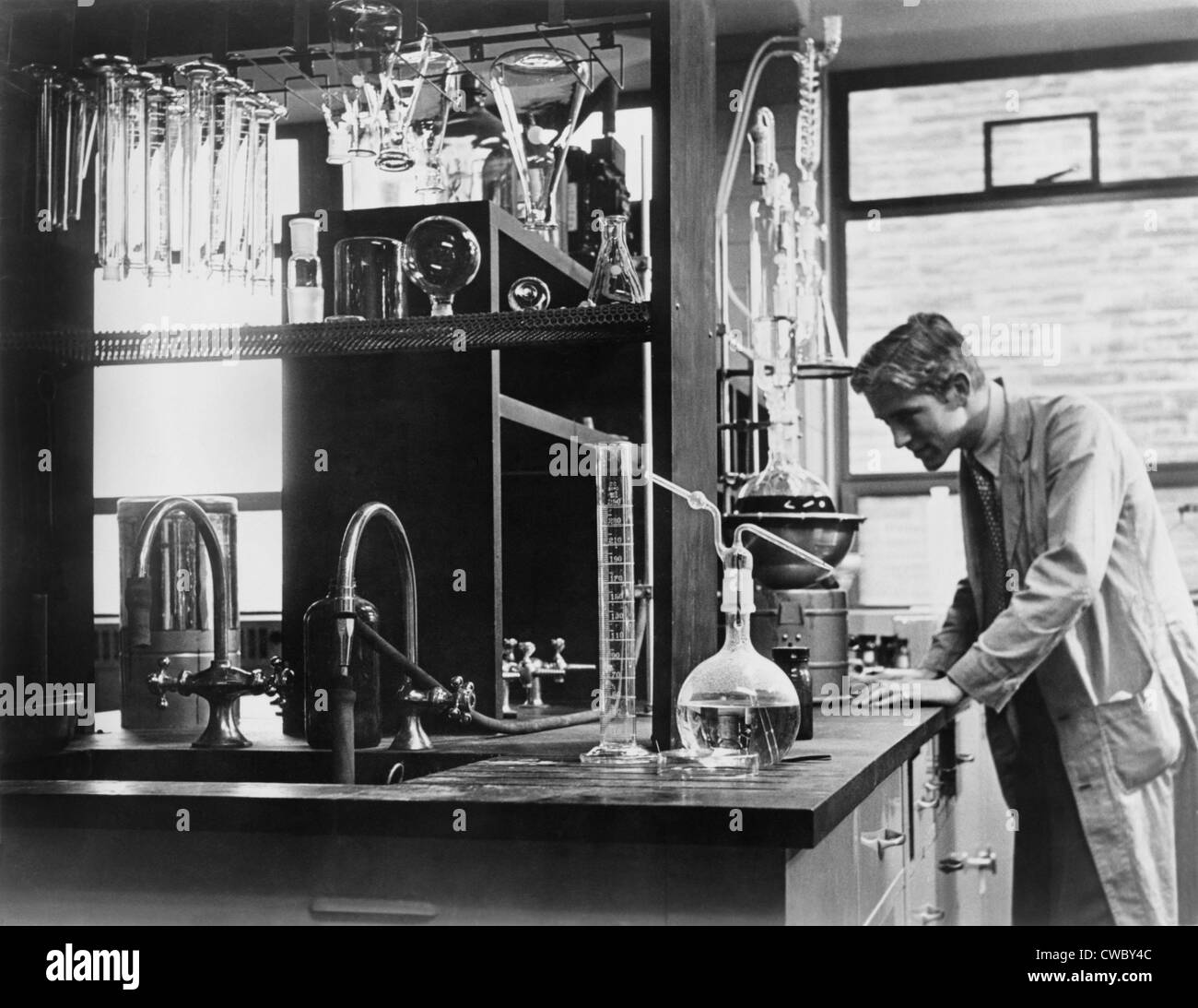 Scientist conducting a laboratory experiment in a cancer research facility in the United States, 1951. - Stock Image