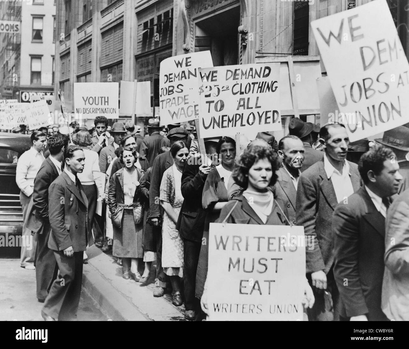 Unemployed New Yorkers demonstrate with signs in front of Emergency Relief Building in 1935. Signs demand clothing, - Stock Image