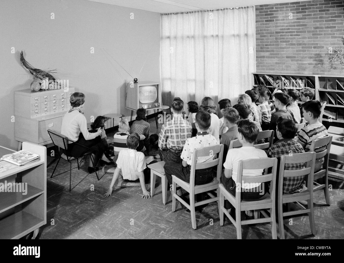 Students and their teacher watch educational television in a school library in Schenectady, New York, 1954. - Stock Image