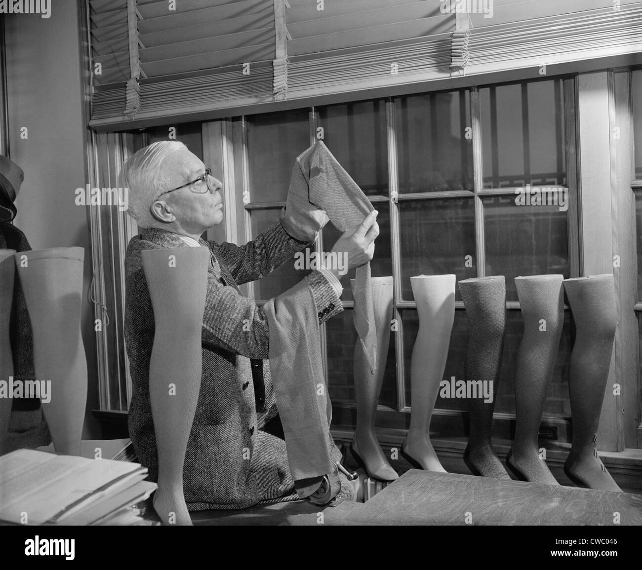 Agriculture Department fabric technician examines the cotton stockings that would replace those made by Japanese - Stock Image