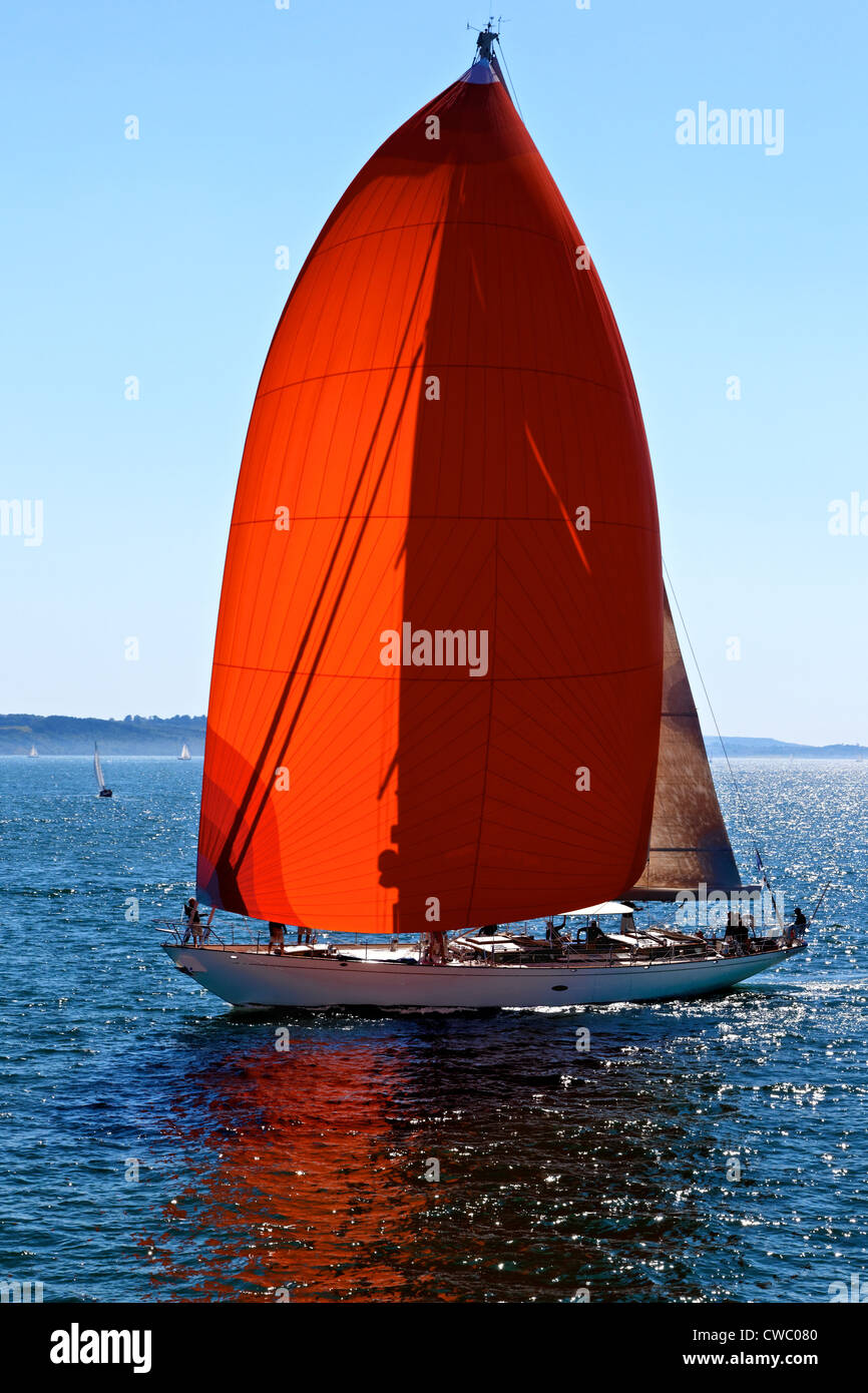 Yacht with red sails on the Solent Hampshire UK - Stock Image