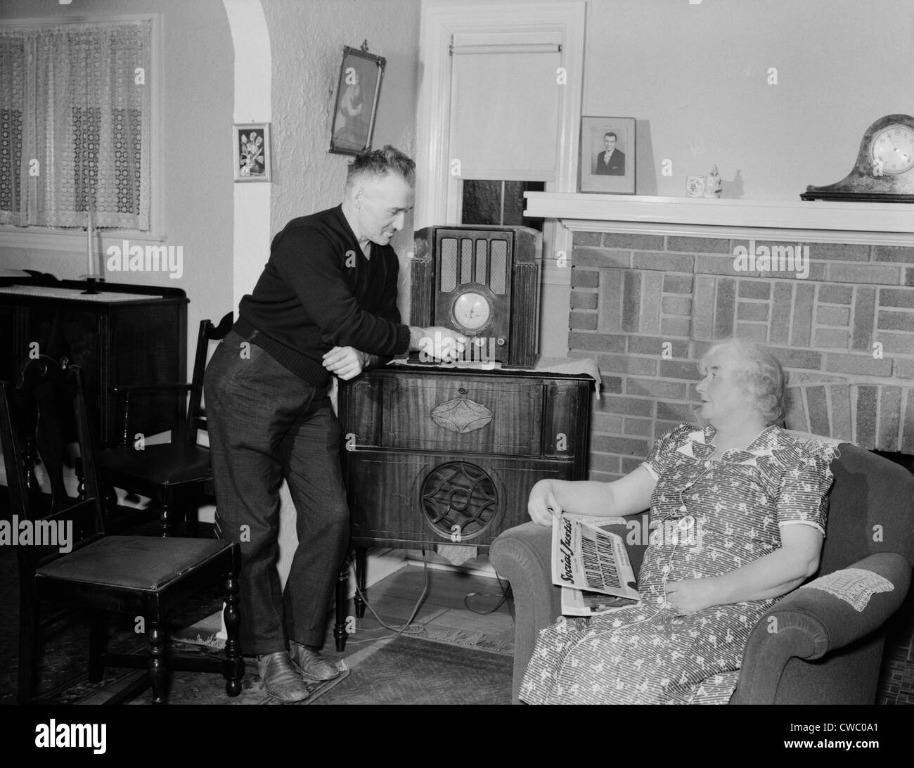 A husband tunes the radio while his wife holds populist right-wing radio priest, Father Coughlin's newspaper - Stock Image