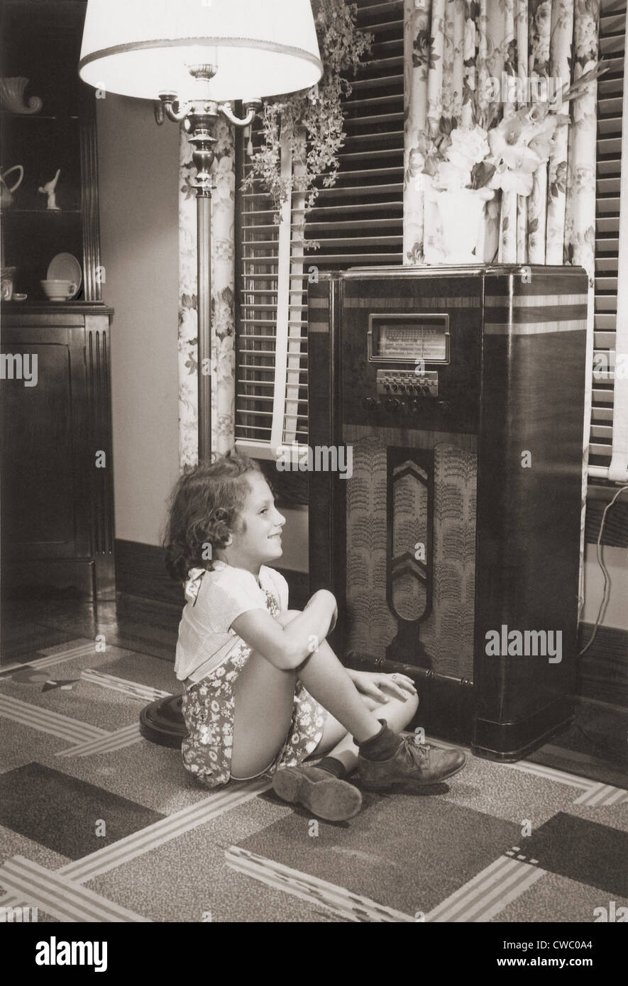 Little girl smiles as she enjoys a radio program in the 1930s. - Stock Image