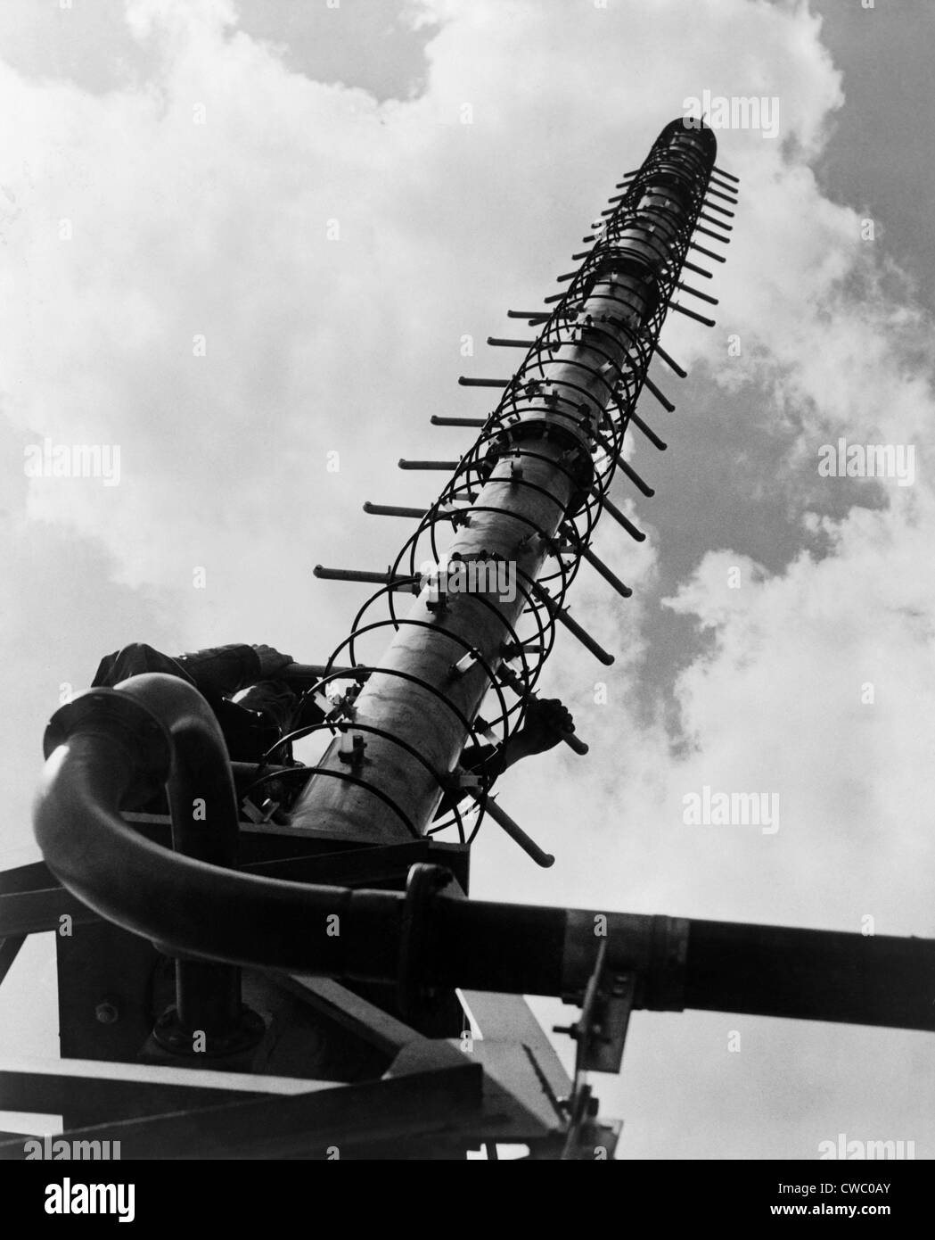 Worker climbing a Helical television antenna developed by General Electric engineers in 1951. Helix antennas consist - Stock Image