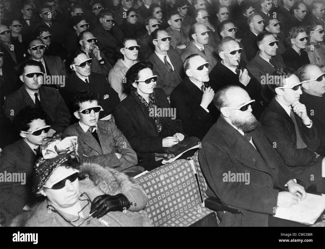 British audience wears smoke-colored glasses to view a 3-D movie in 1954. Stock Photo