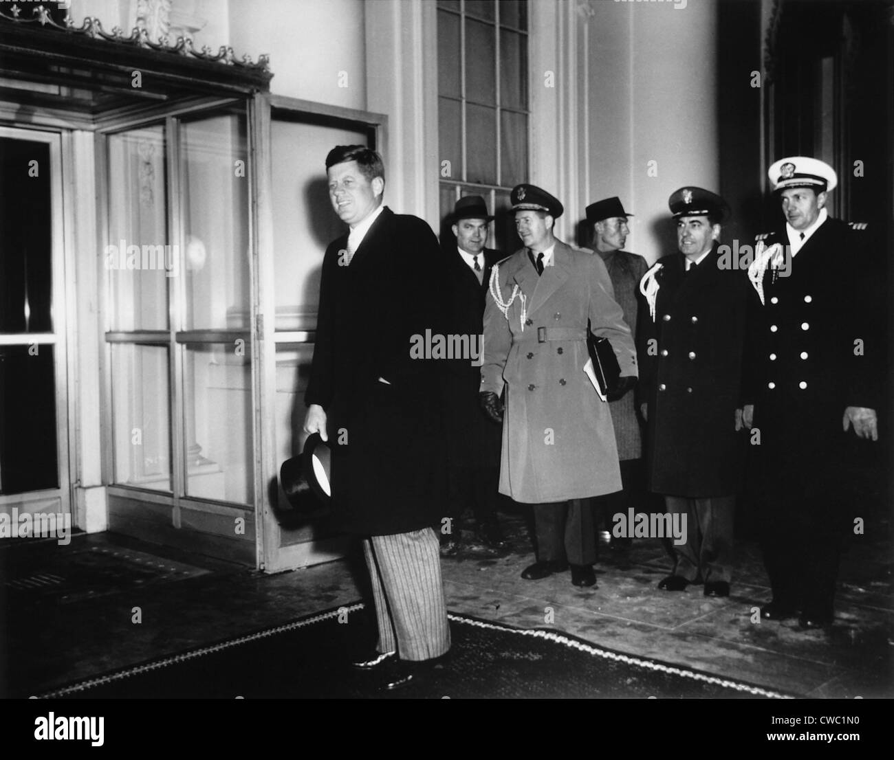 President Kennedy, accompanied by uniformed senior military officers, returns to the White House after attending - Stock Image