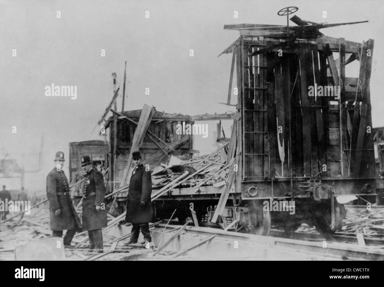 Two policemen and a civilian survey the ruins along the Lehigh Valley Railroad tracks where boxcars were riddled - Stock Image