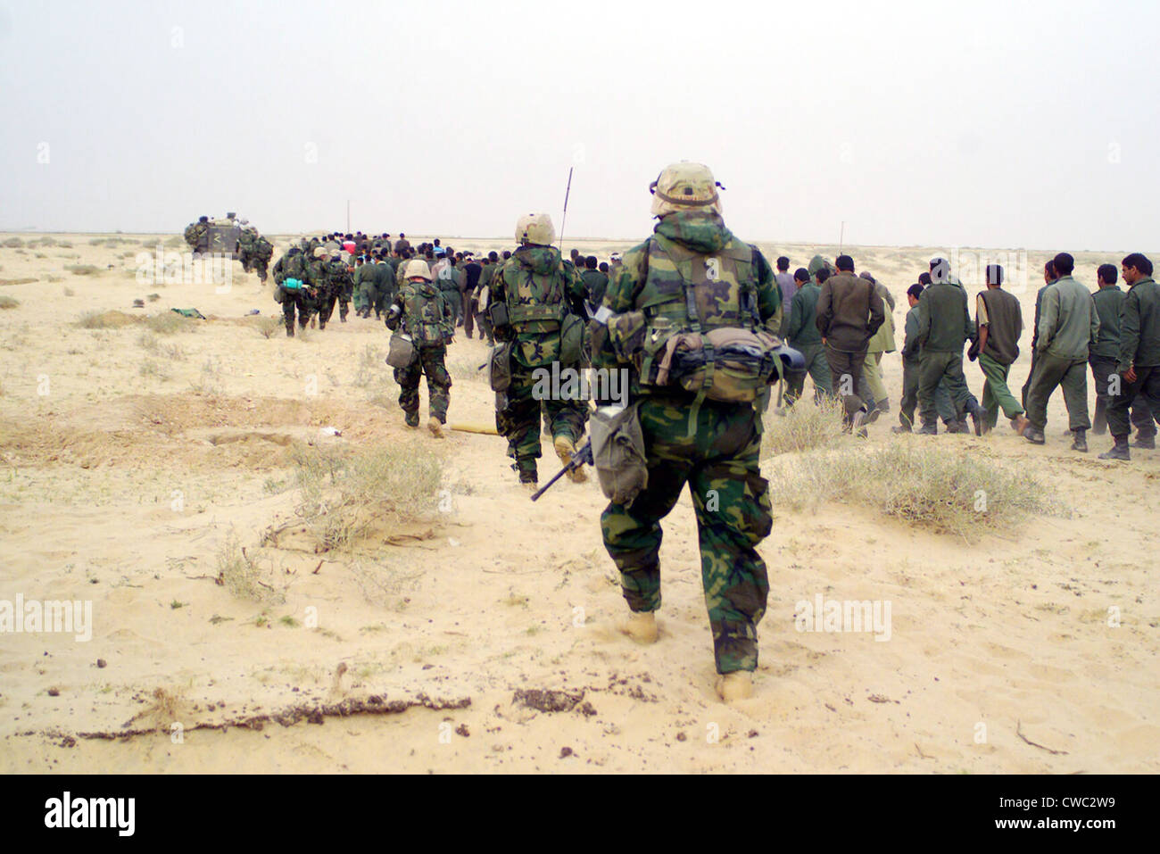 U.S. Marines escort captured enemy prisoners of war to a holding area in the desert of Iraq on March 21 2003 during - Stock Image