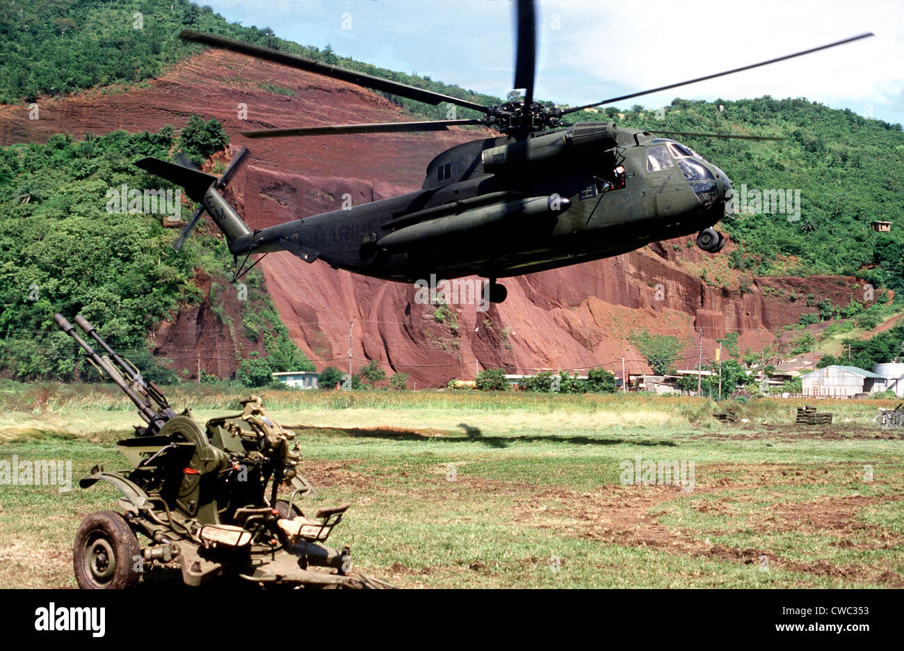 U.S. Marine Corps helicopter hovers near a Soviet anti-aircraft weapon during the U.S. invasion of Grenada in October - Stock Image