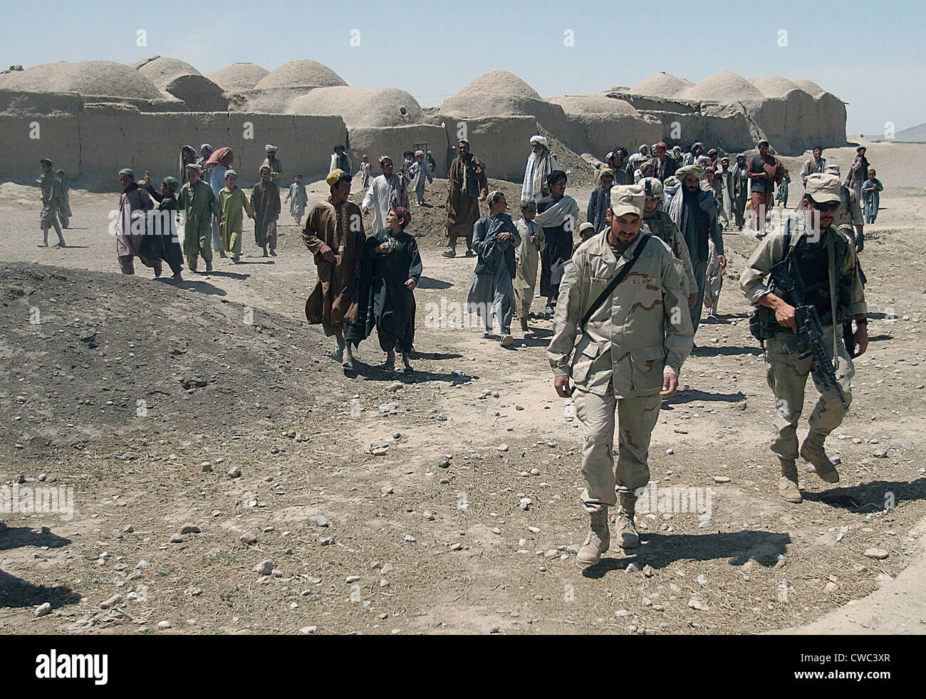 Villagers from Nojoy outside Kandahar International Airport follow the members of the U.S. Army's Tactical Psychological - Stock Image