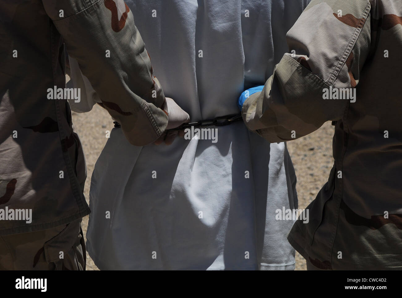 U.S. Sailors both grasping the chain around a detainee's waist escort him to a legal appointment at Camp Delta - Stock Image