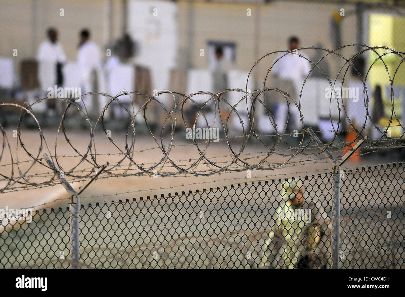 A U.S. Sailor foreground conducts an early morning patrol while detainees dressed in white background at a recreation - Stock Image