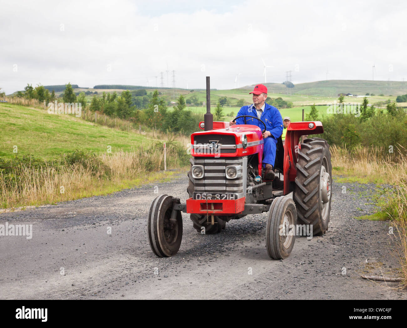 Enthusiast driving a red vintage Massey Ferguson 165 tractor during an  Ayrshire Vintage Tractor and Machine