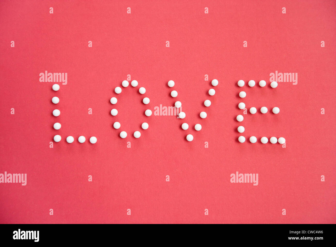 Close-up of push pins spelling love over colored background - Stock Image