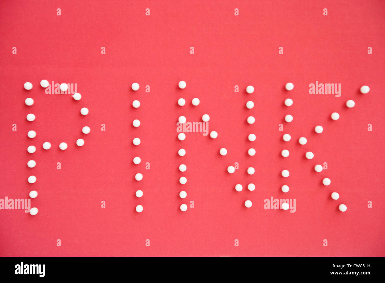 Close-up of push pins spelling pink over colored background - Stock Image