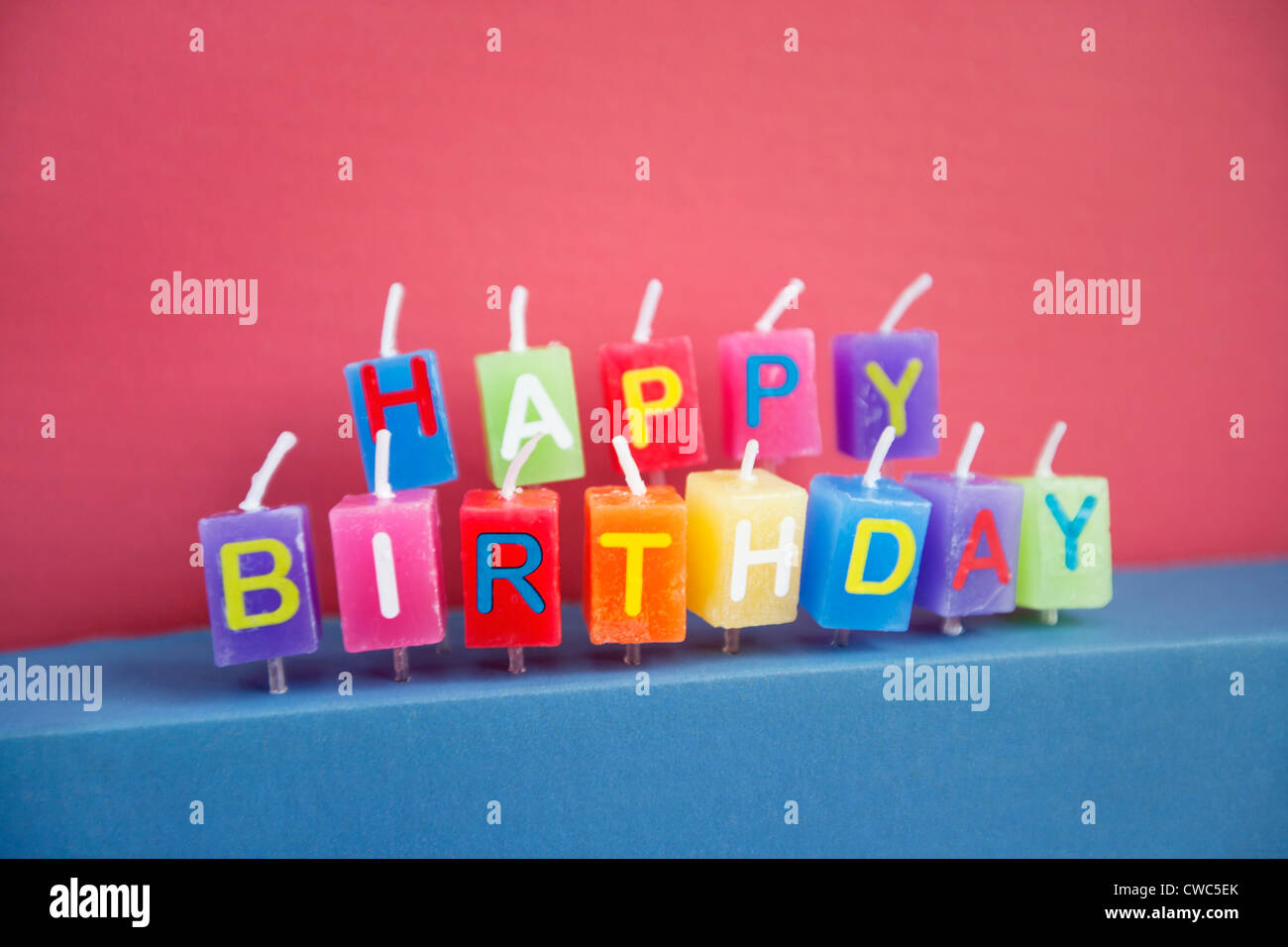Unlit birthday candles over colored background - Stock Image