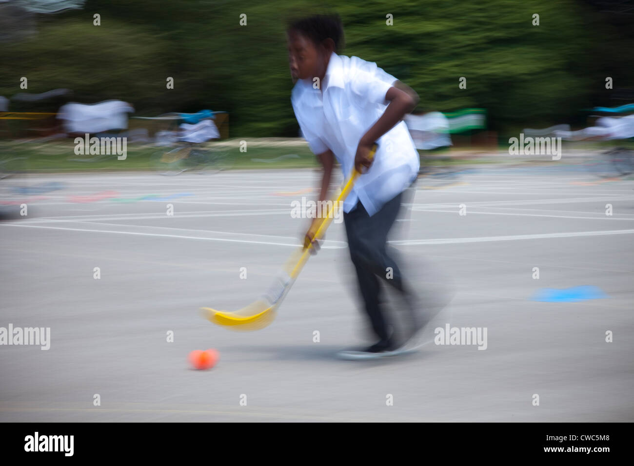 A young Asian boy plays hockey playground of his school UK - Stock Image