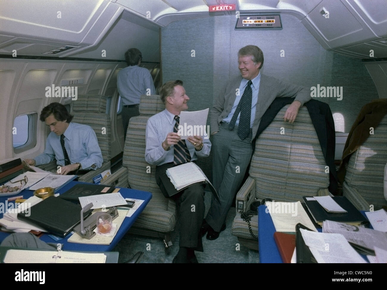 Zbigniew Brzezinski and Jimmy Carter in a relaxed discussion aboard Air Force One while an young staffer works in - Stock Image