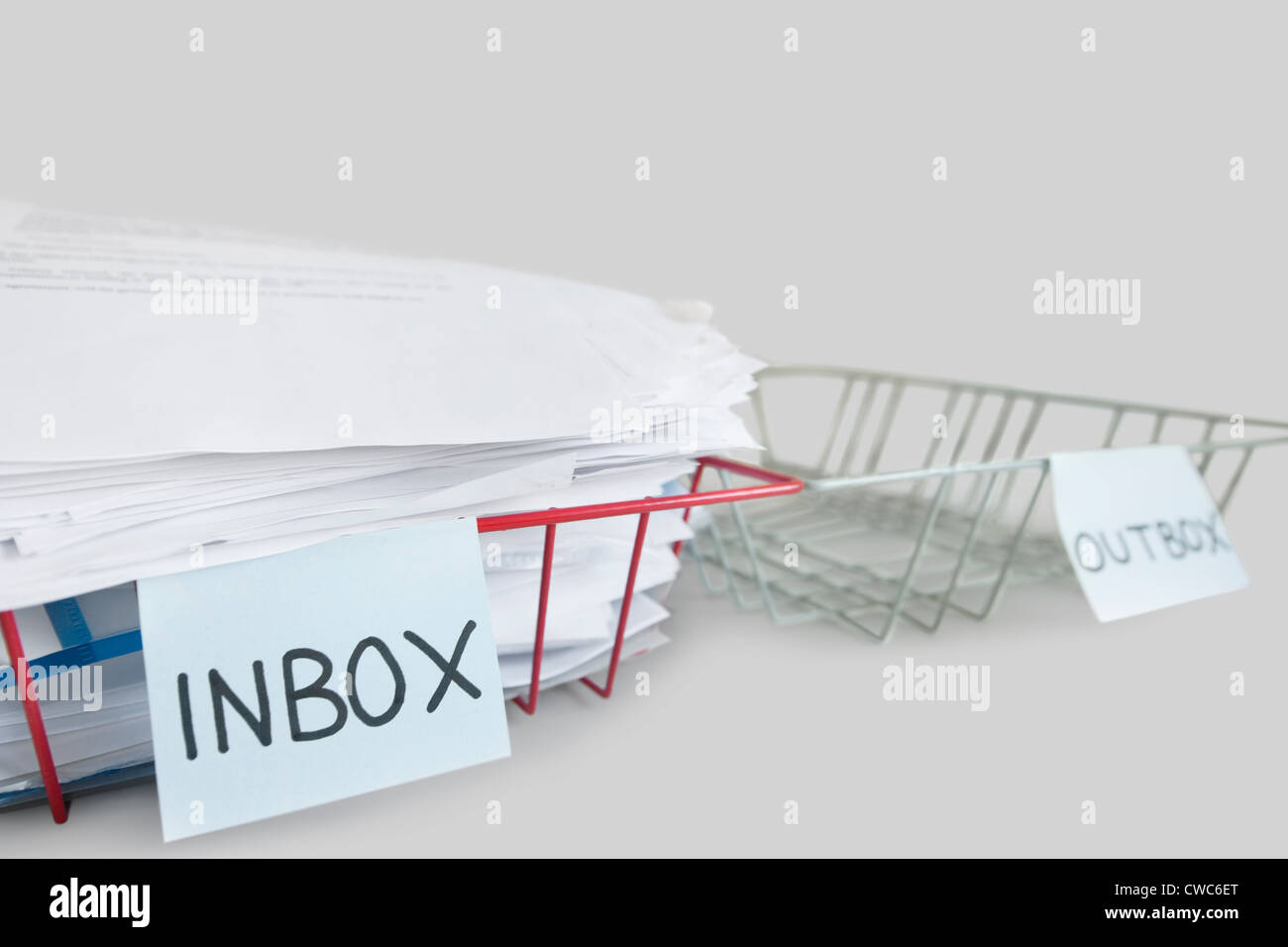 Inbox and outbox trays in an office over white background - Stock Image