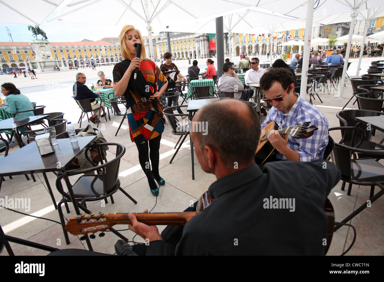 Fado singer accompanied by two guitar players at Terreiro do Paço, Lisbon, Portugal. - Stock Image