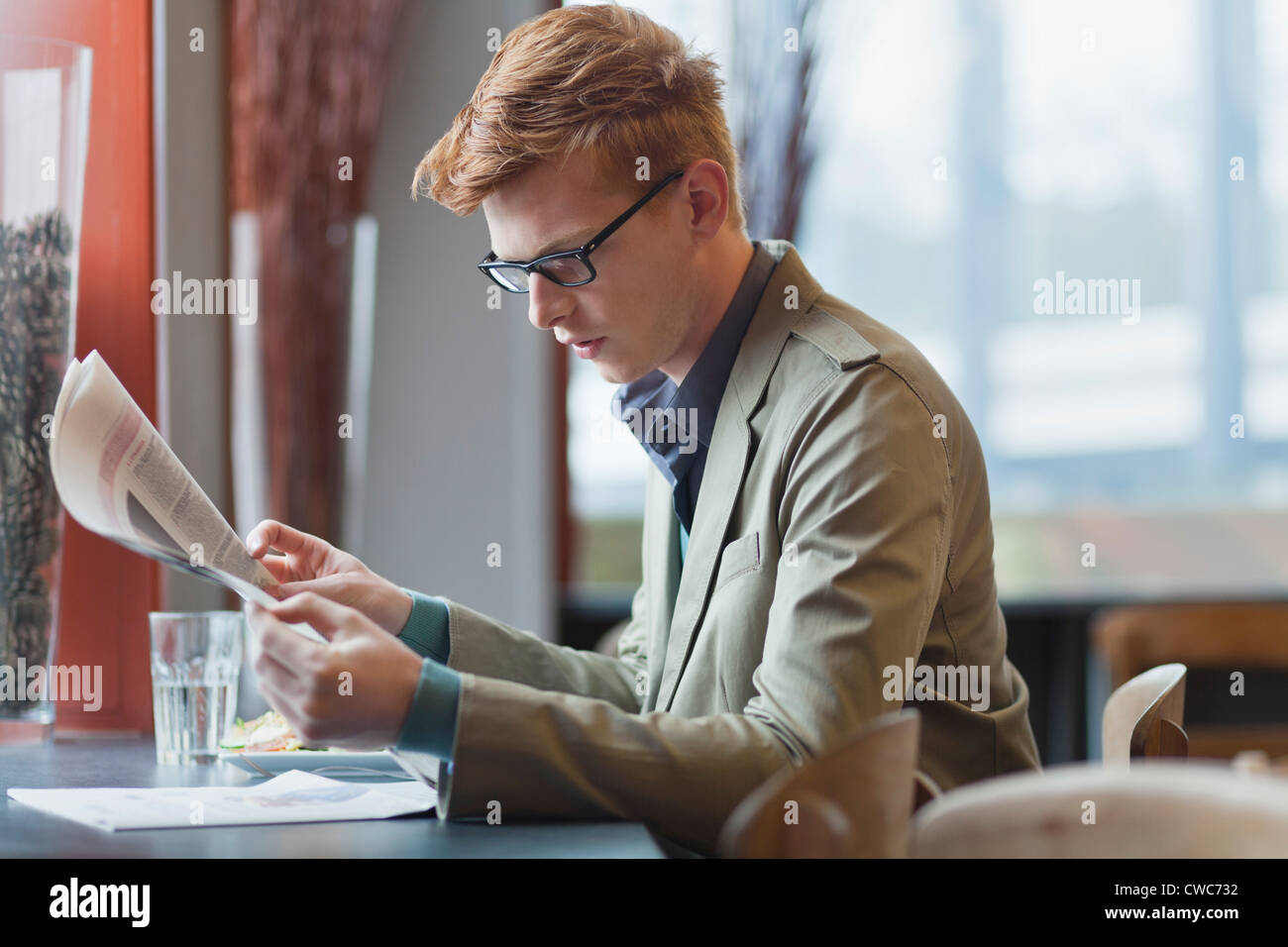 Man sitting in a restaurant and reading a newspaper - Stock Image