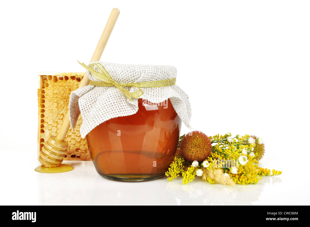 sweet honey in glass jar with wooden honey dripper, fresh honey in comb and bouquet of wild flowers - Stock Image