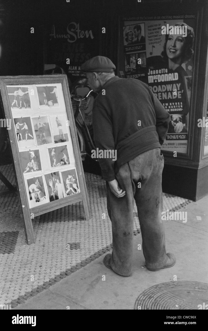 Elderly man with patches clothing looking at stills of Joe Lewis fight. Windsor Locks Connecticut. Oct. 1939. - Stock Image